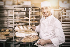 Усмехаясь хлебопек держа поднос хлеба Стоковые Фото