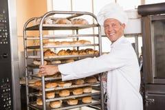 Усмехаясь хлебопек нажимая поднос хлеба Стоковые Изображения