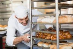 Усмехаясь хлебопек нажимая поднос хлеба Стоковые Фотографии RF