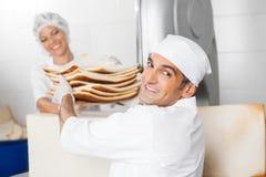 Усмехаясь хлебопек получая отход хлеба от сотрудника Стоковое фото RF