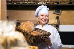 Усмехаясь хлеб работника хлебопекарни предлагая Стоковые Изображения RF