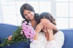 Усмехаясь цветки девушки предлагая к ее матери Стоковое Изображение