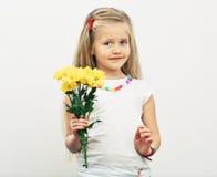 Усмехаясь цветки желтого цвета владением девушки Стоковое фото RF