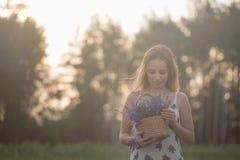 Усмехаясь цветки обнюхивать девушки в поле лаванды Стоковая Фотография