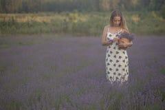 Усмехаясь цветки обнюхивать девушки в поле лаванды Стоковые Изображения