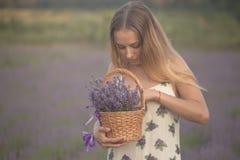 Усмехаясь цветки обнюхивать девушки в поле лаванды Стоковое Фото