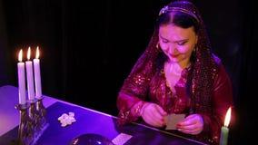 Усмехаясь цыган в волшебном салоне светом горящей свечи читает будущее на картах сток-видео