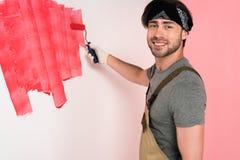 усмехаясь человек в работая стене картины прозодежды и держателя в красном цвете краской стоковые изображения