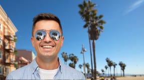Усмехаясь человек в солнечных очках над пляжем Венеции стоковое фото