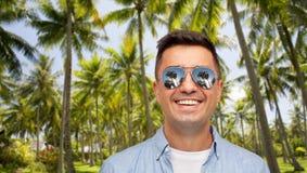 Усмехаясь человек в солнечных очках над тропическим пляжем стоковое фото