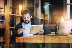Усмехаясь человек держа кредитную карточку пока делающ онлайн покупки Стоковая Фотография RF