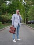 Усмехаясь человек идя на запачканную предпосылку парка Работник дела говоря на телефоне Финансовая концепция стабильности Стоковые Изображения RF