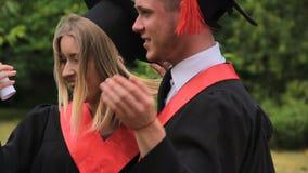 Усмехаясь человек нося женского друга и поворачивая вокруг на выпускную церемонию видеоматериал