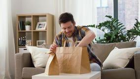 Усмехаясь человек распаковывая на вынос еду дома акции видеоматериалы