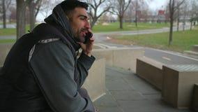 Усмехаясь человек сидит на стенде говоря на телефоне и смотреть море акции видеоматериалы