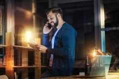 Усмехаясь человек сидя на таблице и говоря на телефоне Стоковые Изображения