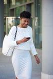 Усмехаясь чернокожая женщина идя снаружи с мобильным телефоном Стоковая Фотография