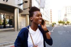Усмехаясь чернокожая женщина идя outdoors и говоря на мобильном телефоне Стоковая Фотография