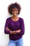 Усмехаясь чернокожая женщина стоя против белой предпосылки Стоковое Изображение