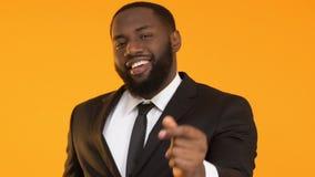 Усмехаясь чернокожий человек в пальцах костюма щелкая, празднуя успешный проект сток-видео