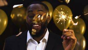 Усмехаясь чернокожий человек с положением под падая confetti, торжеством Бенгалии светлым сток-видео