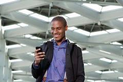 Усмехаясь черный бизнесмен усмехаясь и смотря мобильный телефон Стоковые Фотографии RF