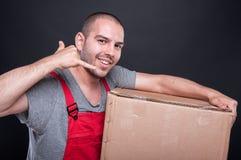 Усмехаясь человек движенца держа показ коробки вызывает меня Стоковые Фото
