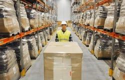 Усмехаясь человек в грузе загрузки защитного шлема на складе Стоковое Изображение RF