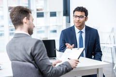 Усмехаясь человек в костюме и eyeglasses показывать и смотря бизнесмена с доской сзажимом для бумаги Стоковые Фотографии RF