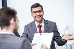 Усмехаясь человек в костюме и eyeglasses показывать и смотря бизнесмена с доской сзажимом для бумаги Стоковая Фотография