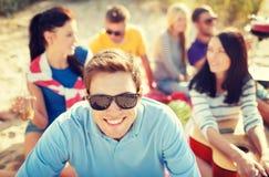 Усмехаясь человек в солнечных очках на пляже Стоковые Фотографии RF