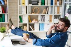 Усмехаясь человек говоря телефоном на проломе в офисе Стоковые Фото