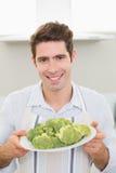 Усмехаясь человек держа плиту брокколи в кухне Стоковые Изображения RF