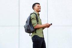 Усмехаясь человек держа умный телефон с рюкзаком стоковые изображения