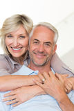Усмехаясь человек женщины обнимая зрелый от заднего на софе Стоковые Изображения RF