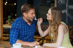 Усмехаясь человек женщины подавая пока сидящ на таблице Стоковое фото RF