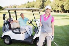 Усмехаясь человек зрелой женщины готовя в багги гольфа Стоковые Изображения RF