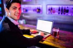 Усмехаясь человек используя компьтер-книжку с стеклом пива на таблице на счетчике бара Стоковое Изображение