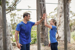Усмехаясь человек и женщина давая максимум 5 во время полосы препятствий Стоковые Изображения