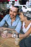 Усмехаясь человек и женщина говоря в кафе Стоковое фото RF