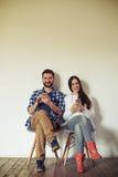 Усмехаясь человек и женщина сидят на стульях с smartphones Стоковые Изображения