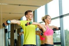 Усмехаясь человек и женщина с гантелями в спортзале Стоковые Фото