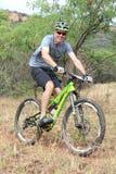 Усмехаясь человек наслаждаясь outdoors ездой на гонке горного велосипеда Стоковое фото RF