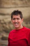 Усмехаясь человек на скалах песка Стоковая Фотография RF