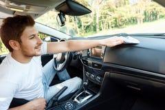 Усмехаясь человек обтирая пыль внутри автомобиля Стоковое Изображение