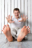 Усмехаясь человек показывает пальцы сидя около стены Стоковые Фото