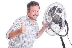 Усмехаясь человек показывая как перед дуя охладитель Стоковое фото RF