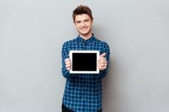 Усмехаясь человек показывая пустой экран планшета стоковое фото