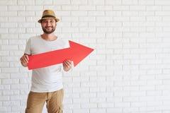Усмехаясь человек стоящ и держащ большая красная стрелка Стоковые Фото