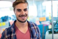 Усмехаясь человек стоя против липких примечаний на стеклянной стене в офисе Стоковое Изображение RF